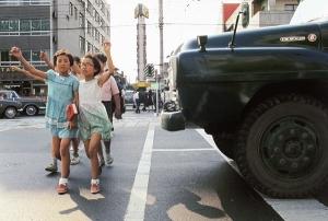Bambine alzano la mano mentre attraversano la strada Tokyo 1970